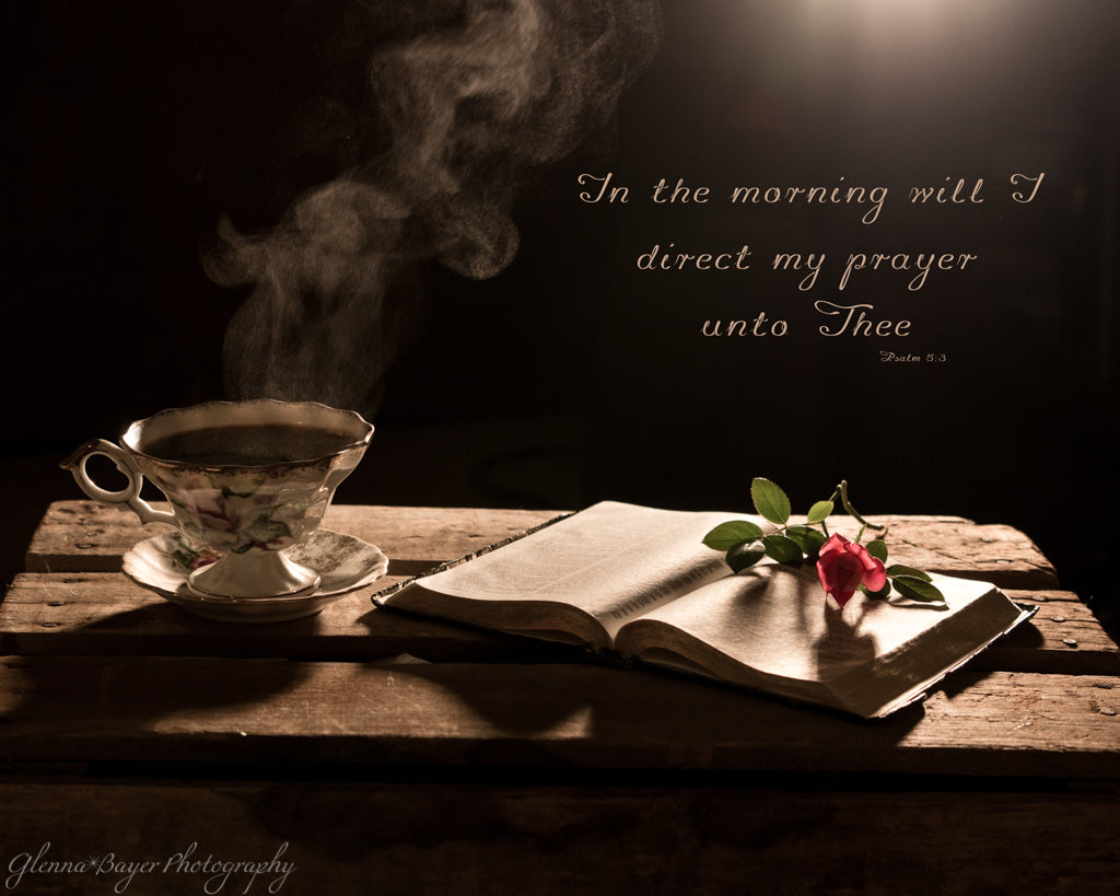 Steaming cup of coffee beside open Bible with scripture verse