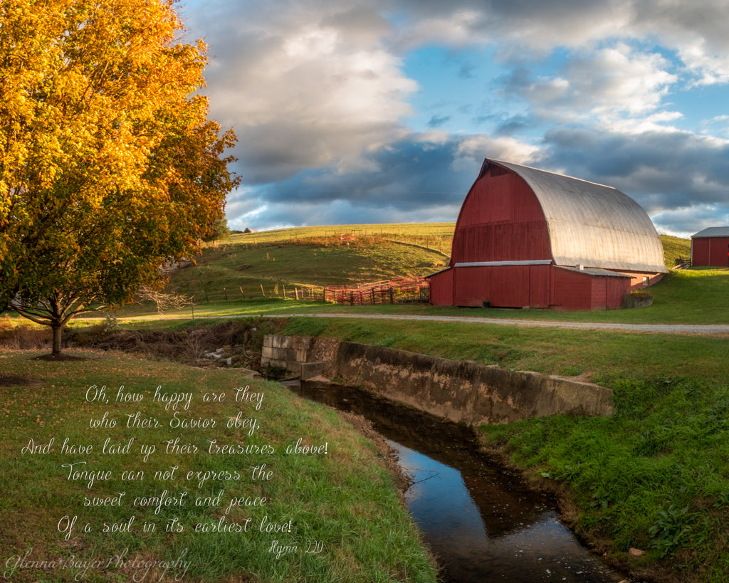 Red barn beside stream in Autumn with song verse