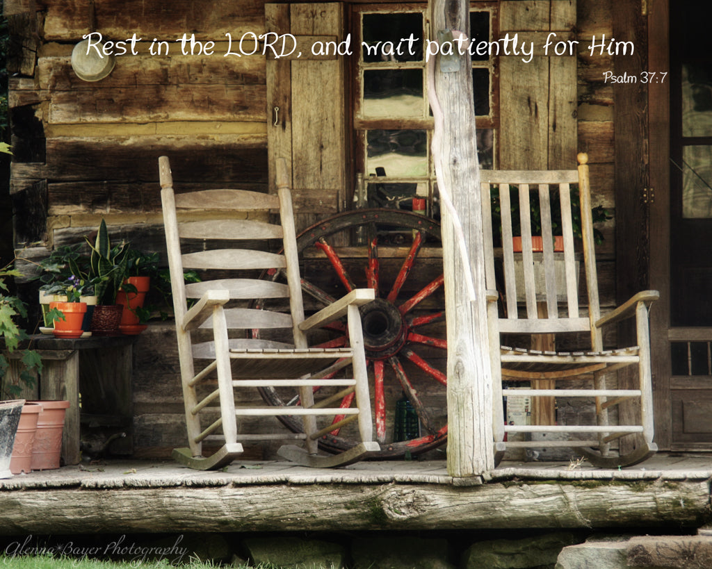 Old wooden rockers on front porch of log cabin with scripture verse