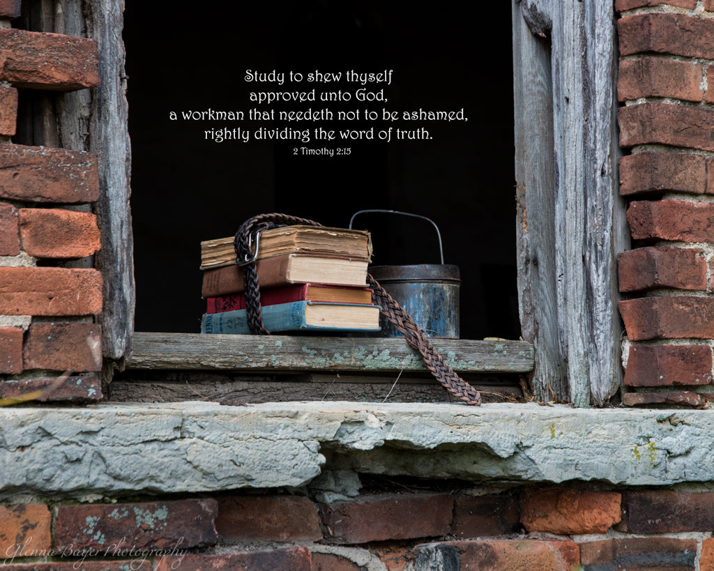 Old school books in window sill of abandon brick one room schoolhouse with scripture verse