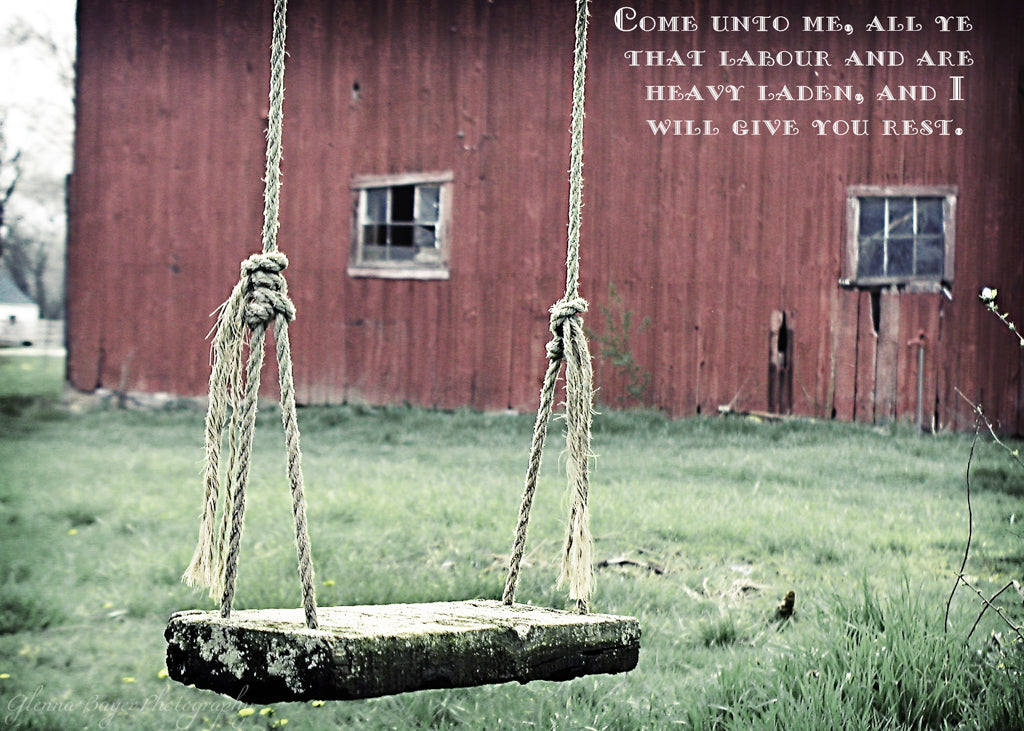 Old wooden rope swing and red barn with scripture verse