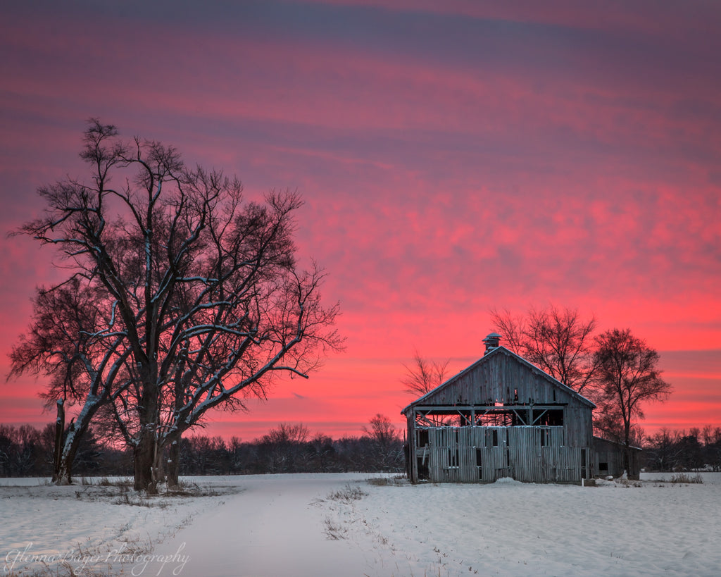 Old wooden barn in snow against dramatic pink sunset