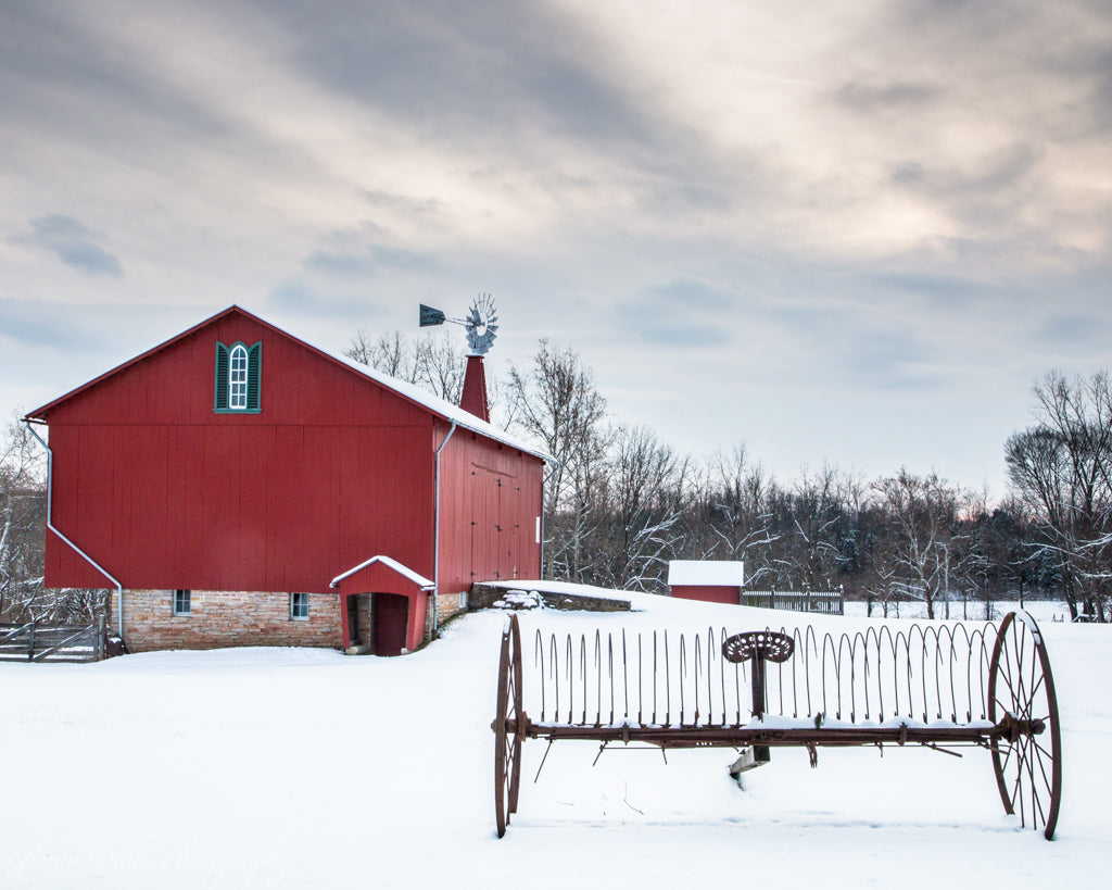 Farming rake and red barn in snow at Carriage Hill Metro Park, Ohio