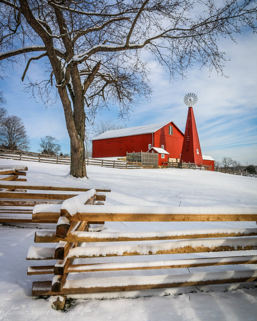 Red barn and wooden fence in snow