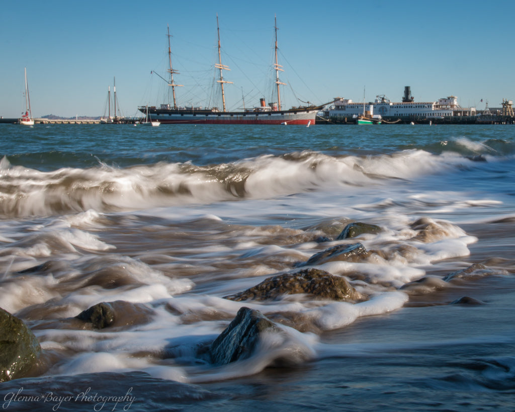 Waves rushing over rocks on beach and boats docked in San Francisco, California morning