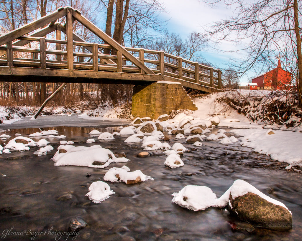 Snowy Stream, wooden bridge, and red barn at Carriage Hill Metro Park in Ohio