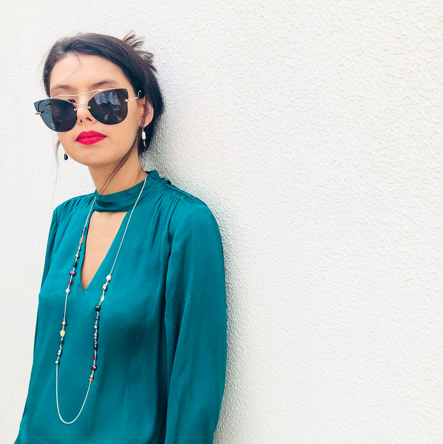 Image of model wearing Leoni & Vonk one of a kind jewellery wearing a green shirt and leaning against a white wall