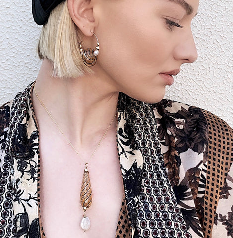 Image of Model wearing Leoni & Vonk venetian bead and pearl necklace, a Zara jacket and a Murley & Co hat