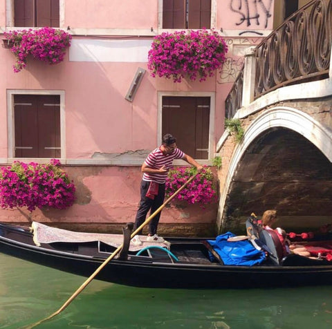 Image of a gondolier in Venice and a pink wall with flowers