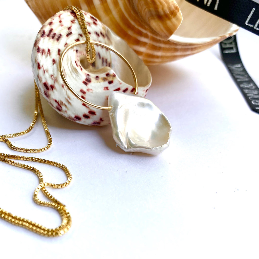 Leoni & Vonk gold ring and keshi pearl necklace near Leoni & Vonk ribbon and sea shells