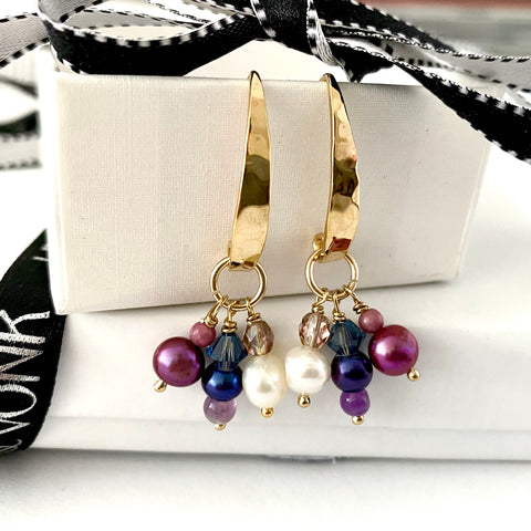 Leoni & Vonk gold charm earrings photographed near Leoni & Vonk ribbon