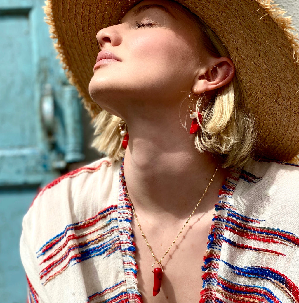 Model wearing Leoni & Vonk sea bamboo jewellery, straw hat and red and cream kimono