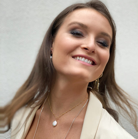 Model wearing Leoni & Vonk Lulu pearl necklace and a white jacket