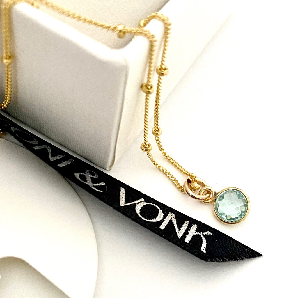 Leoni & Vonk aquamarine gold drop necklace photographed near a white box and Leoni & Vonk ribbon