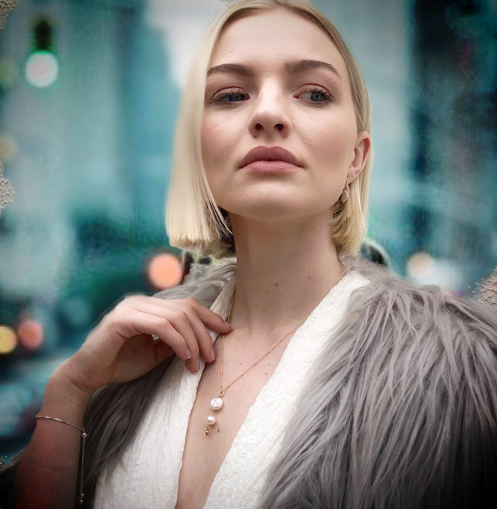Model wearing Leoni & Vonk keshi pearl necklace and grey furry jacket