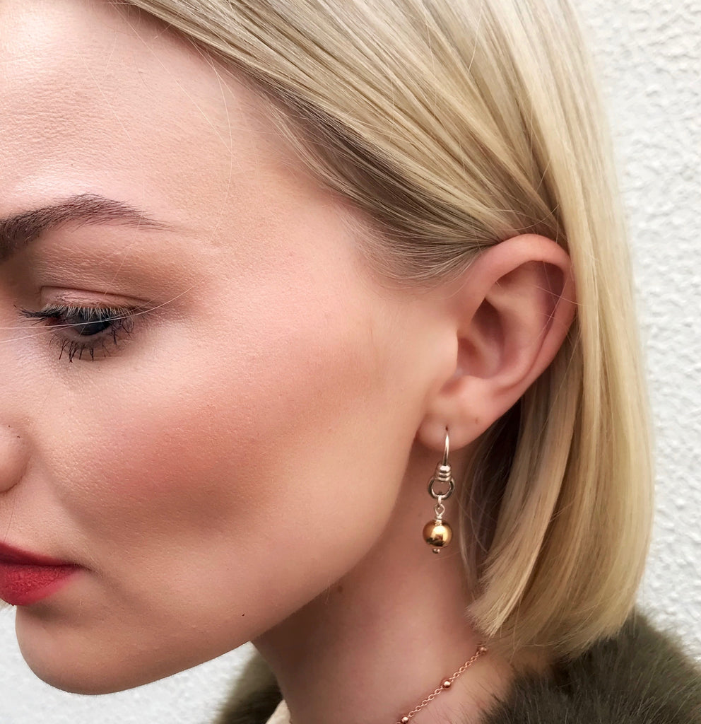 Model wearing Leoni & Vonk earring standing against a white wall