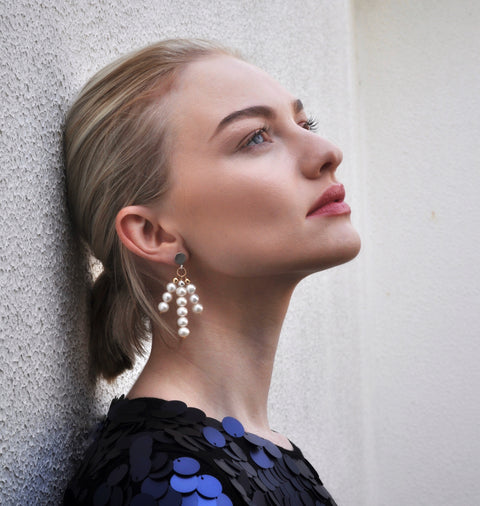 Model wearing Leoni & Vonk statement pearl earrings and a blue Zara sequin dress
