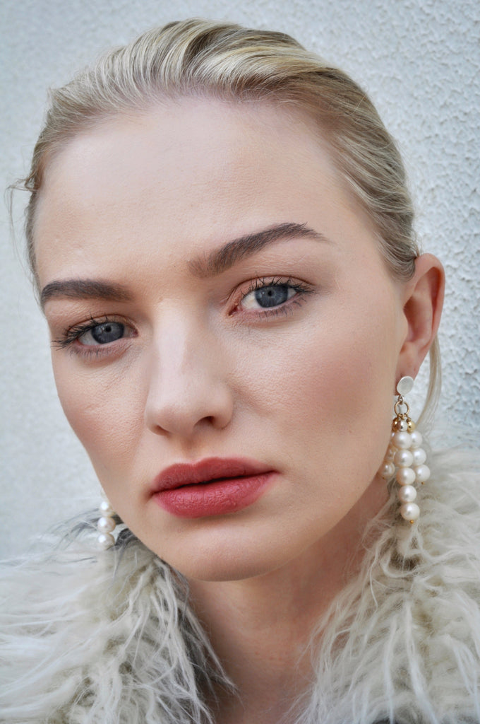 Model wearing Leoni & Vonk statement pearl earrings and a white Zara fluffy jacket