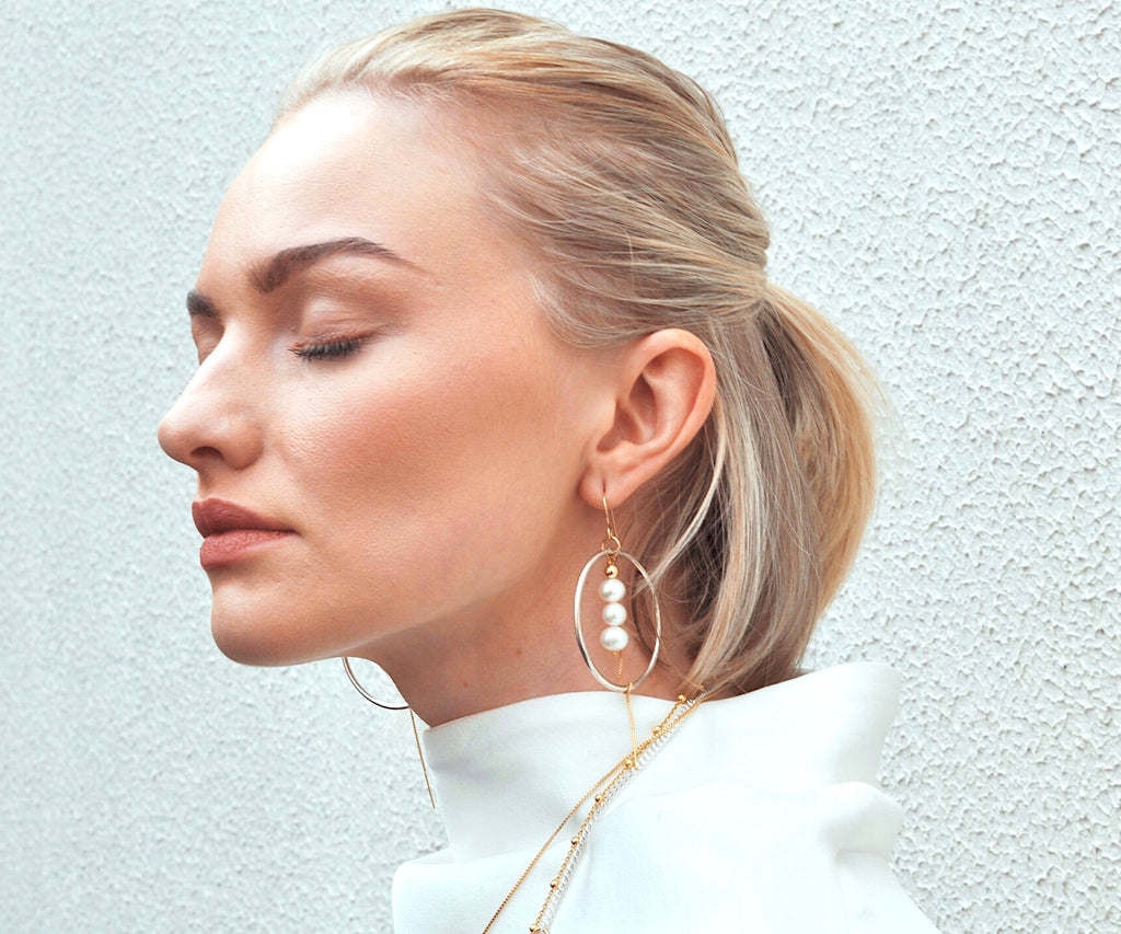 Model wearing Leoni & Vonk large statement earrings and a white Ellery dress leaning against a white wall