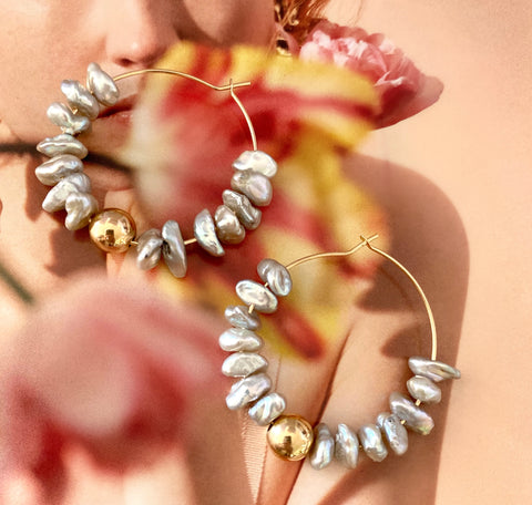 Leoni & Vonk Polly keshi pearl and gold hoop earrings photographed on a magazine page