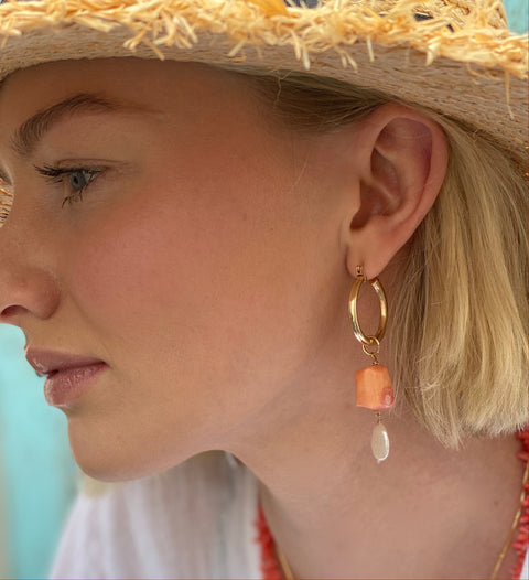 Model wearing Leoni & Vonk coral and pearl jewellery, straw hat and white Zara shirt