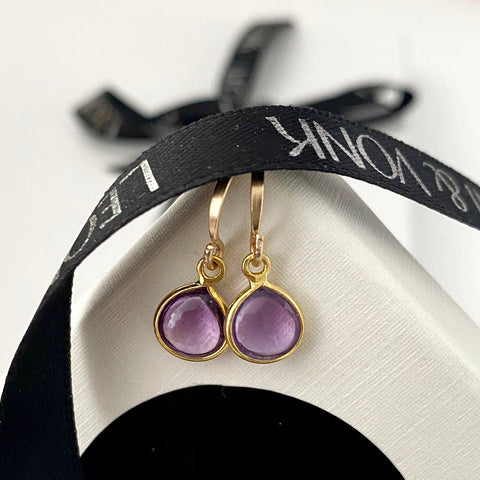 Leoni & Vonk amethyst and gold fill earrings photographed on a white box with Leoni & Vonk ribbon