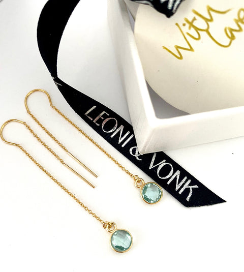 Leoni & Vonk aquamarine gold chain earrings photographed near a white box and Leoni & Vonk ribbon