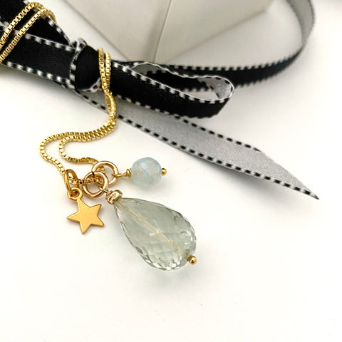 Leoni & Vonk faceted aquamarine and gold star necklace photographed with black ribbon