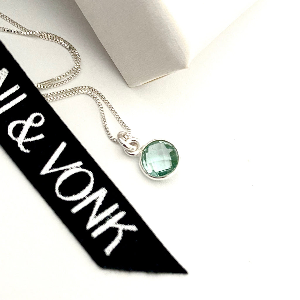 Leoni & Von aquamarine silver dot necklace photographed against a white background and Leoni & Vonk ribbon.