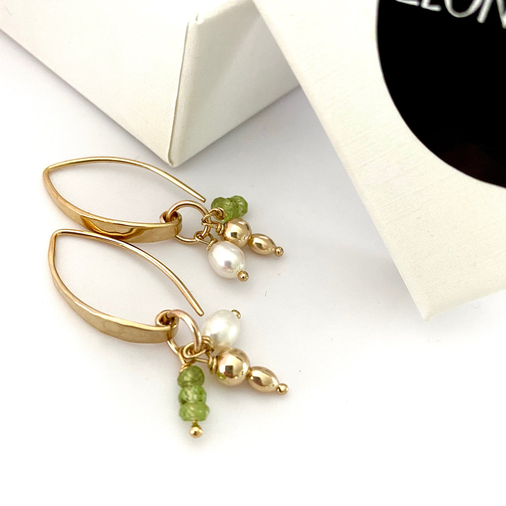 Leoni & Vonk peridot, gold, pearl charm earrings photographed near a box
