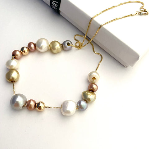 Leoni & Vonk pearl and gold necklace photographed near a white box and Leoni & Vonk ribbon