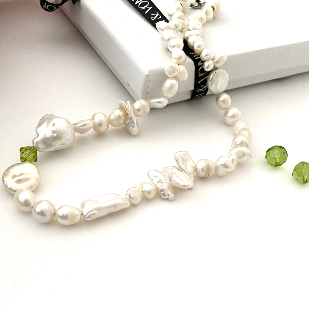 Leoni and Vonk pearl and green swarovski pearl necklace photographed near a Leoni & Vonk box and ribbon