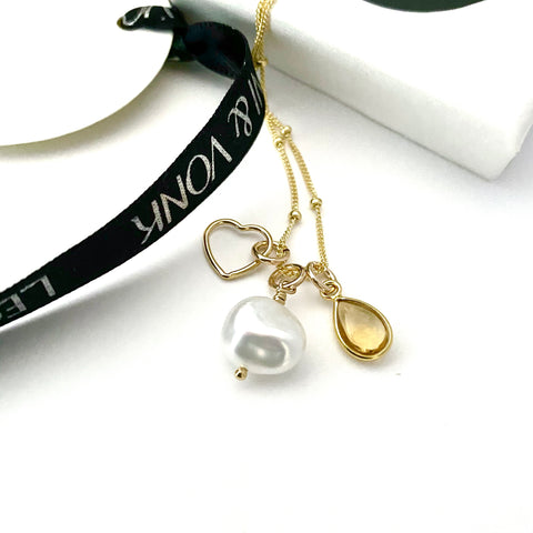 Leoni & Vonk citrine, pearl and heart gold necklace photographed near a white box and Leoni & Vonk ribbon
