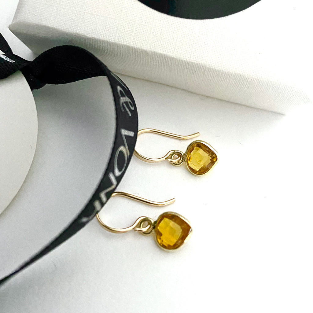 Leoni & Vonk citrine heart earrings photographed near a white box and Leoni & Vonk ribbon