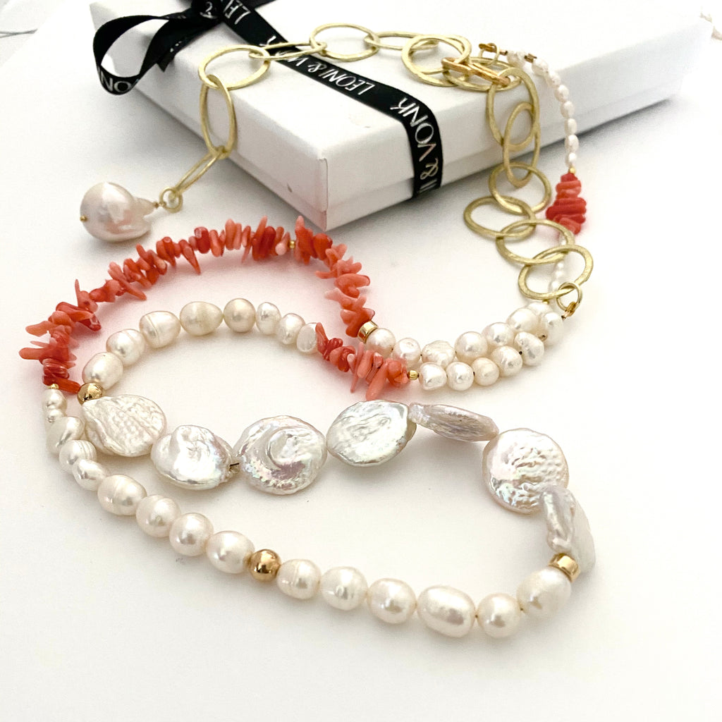 Leoni & Vonk coral and pearl long necklace photogrpahed near a Leoni & Vonk box and ribbon