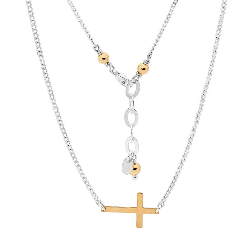 Leoni & Vonk sterling silver and gold cross necklace on a white background