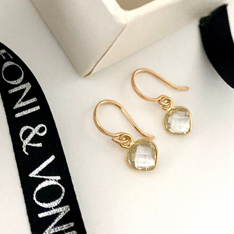 Leoni & Vonk crystal heart earrings photographed near a white box and Leoni & Vonk ribbon