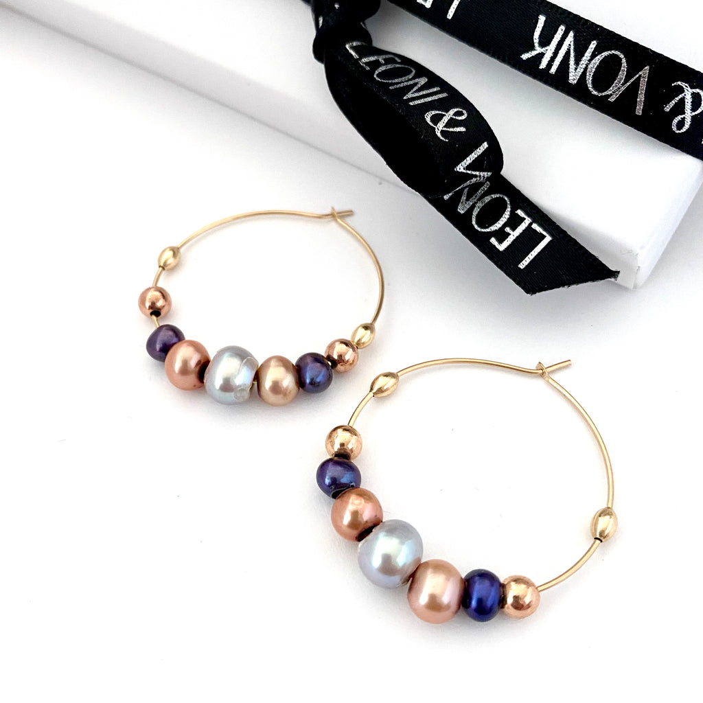 Leoni & Vonk pearl gold hoop earrings photographed near Leoni & Vonk ribbon
