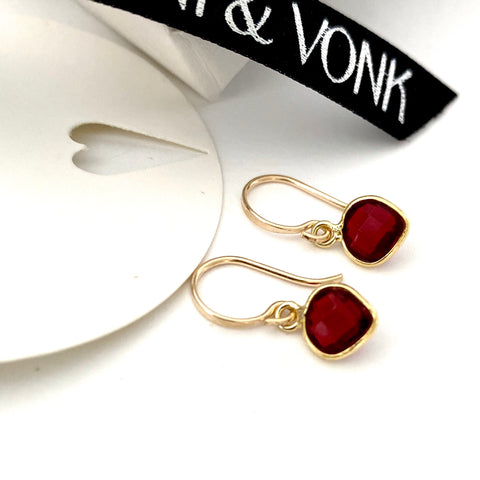 Leoni & Vonk garnet and gold heart earrings photographed near  Leoni & Vonk ribbon