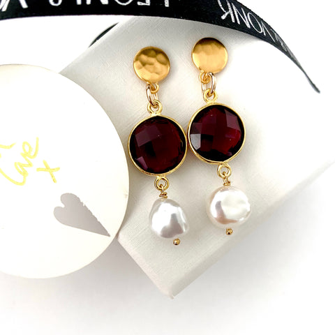 Leoni & Vonk garnet, gold and white keshi pearl stud earrings photographed near a white box and Leoni & Vonk ribbon
