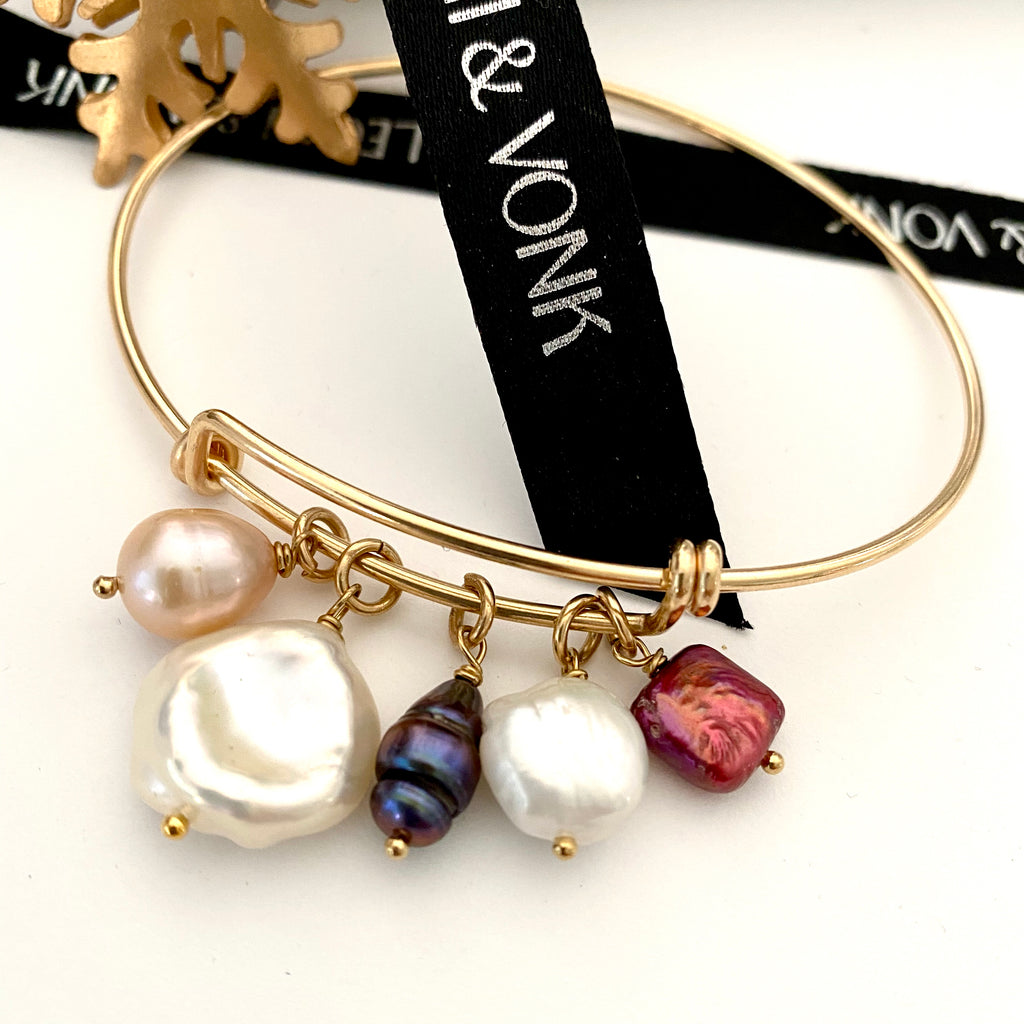 Leoni & Vonk expandable gold bracelet with pearls photographed near Leoni & Vonk ribbon