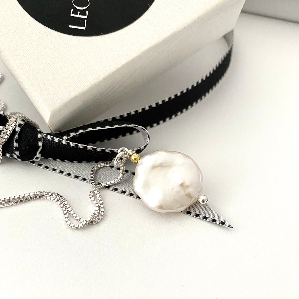 Leoni & Vonk large keshi pearl on sterling silver chain  photogrpahed near black ribbon