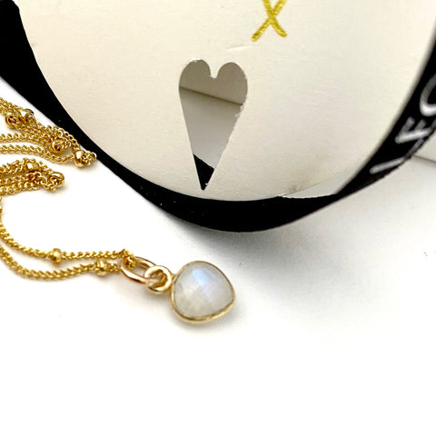 Leoni & Vonk moonstone heart gold necklace photographed near Leoni & Vonk ribbon