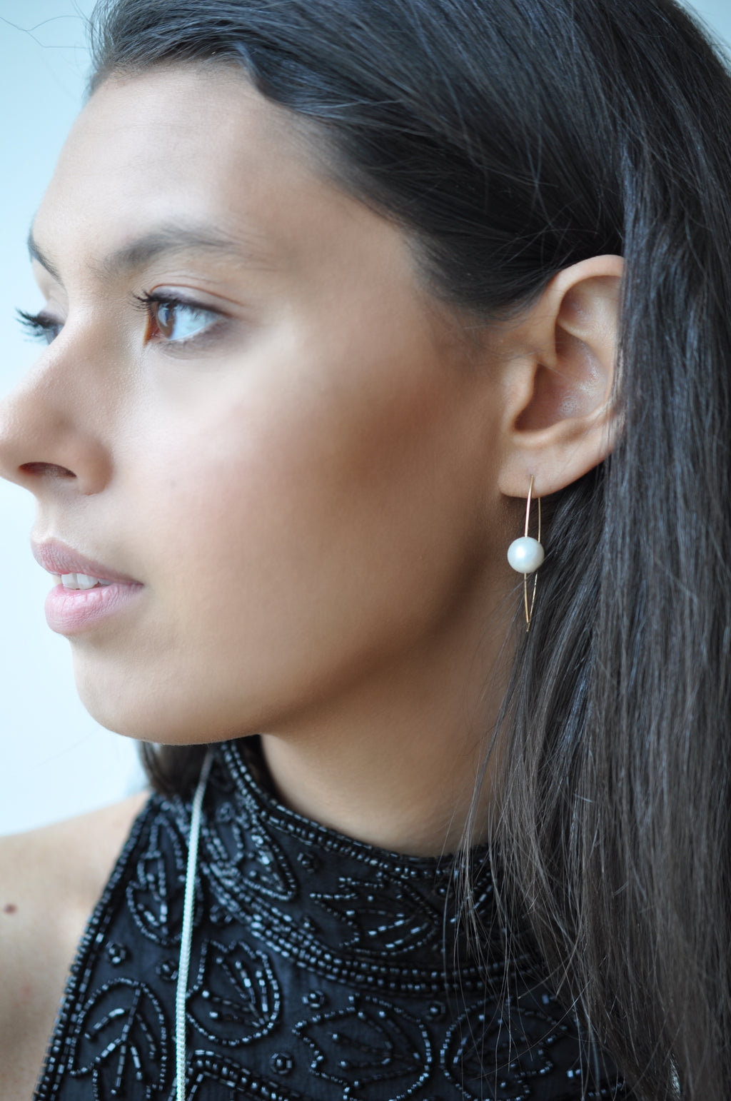 Model wearing pink jumper and Leoni & Vonk pearl ear wire earring