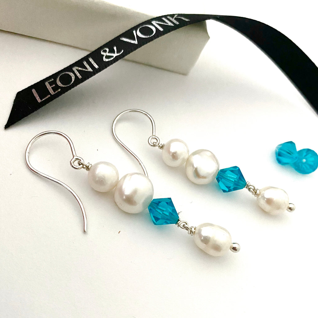 Leoni & Vonk swarovski crystal and white pearl earrings on a white background and near Leoni & Vonk ribbon