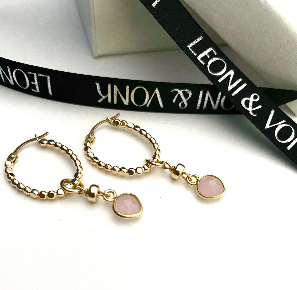 Leoni & Vonk gold hoop earrings with pink chalcedony heart drops photographed near Leoni & Vonk ribbon
