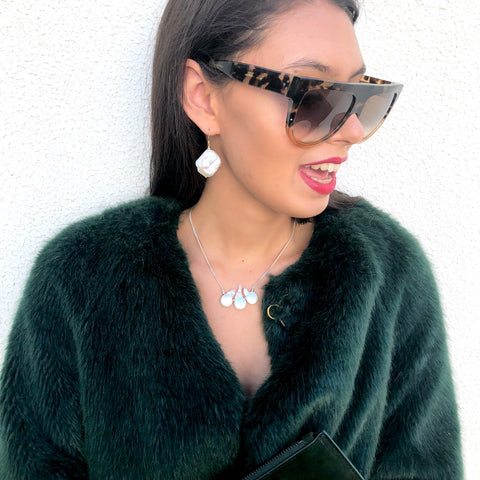 Model wearing sunglasses, green coat and Leoni & Vonk keshi pearl necklace