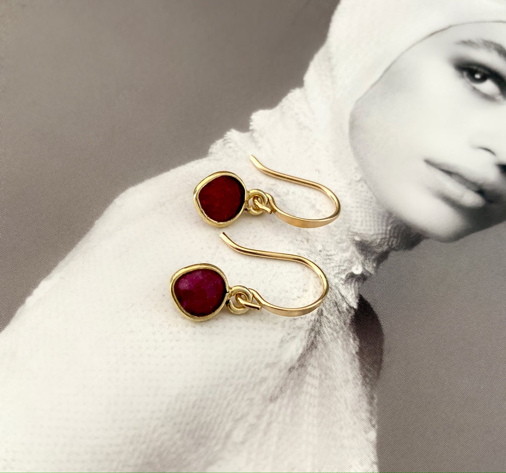 Leoni & Vonk ruby and gold heart earrings photographed on a magazine page