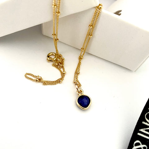 Leoni & Vonk sapphire heart on a gold chain necklace photographed near a white box