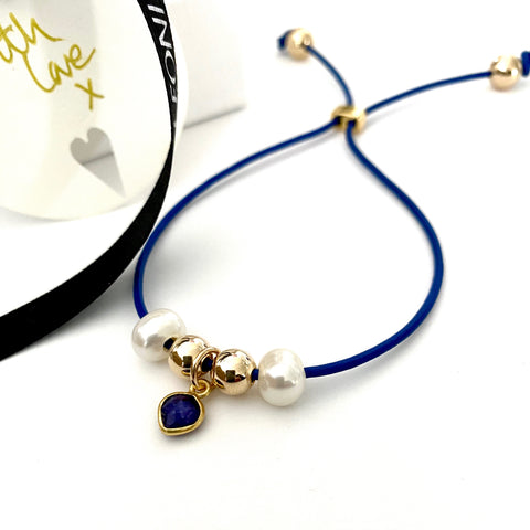 Leoni & Vonk sapphire heart, pearls, and gold leather bracelet photographed near Leoni & Vonk ribbon